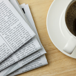 picture of a stack of newspapers and a cup of coffee